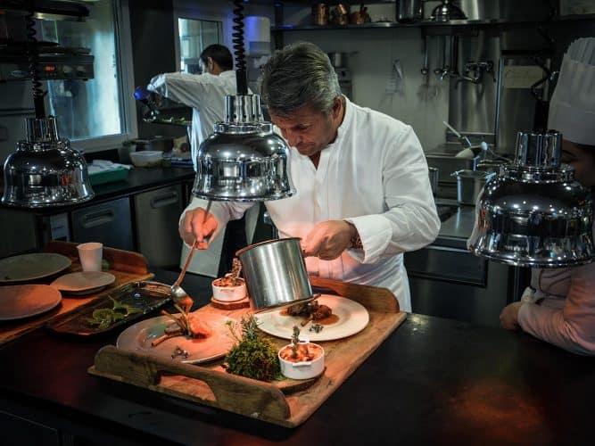 Edouard Loubet en cuisine, concentré sur son dressage - © 180°C  Photographie Manu Rodriguez
