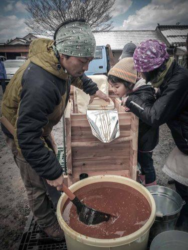 Le koji mis à fermenter dans des récipients, est versé dans des sacs en toile pour être ensuite pressé. - © 180°C - Photographie Julia Bouchet