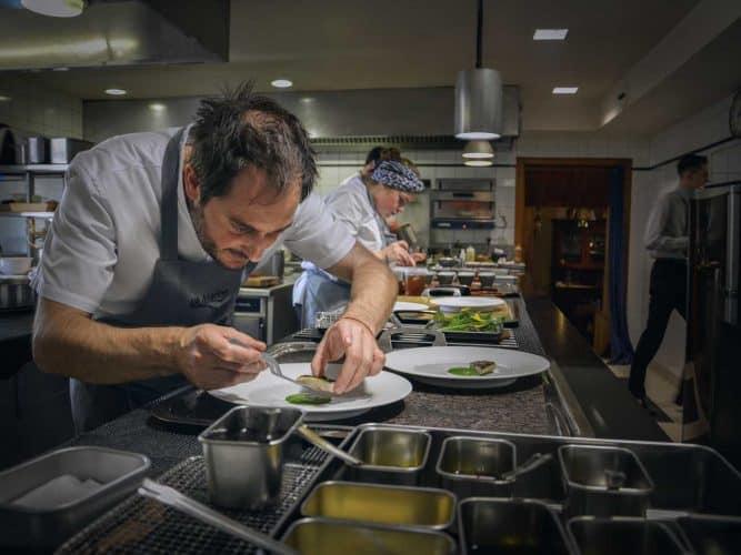 """L'équipe en plein service, Alexandre prépare les filets de """"maquereau de pays brûlé à la braise, condiment du jardin et myrtilles"""" © 180°C - Photographie Manu Rodriguez"""
